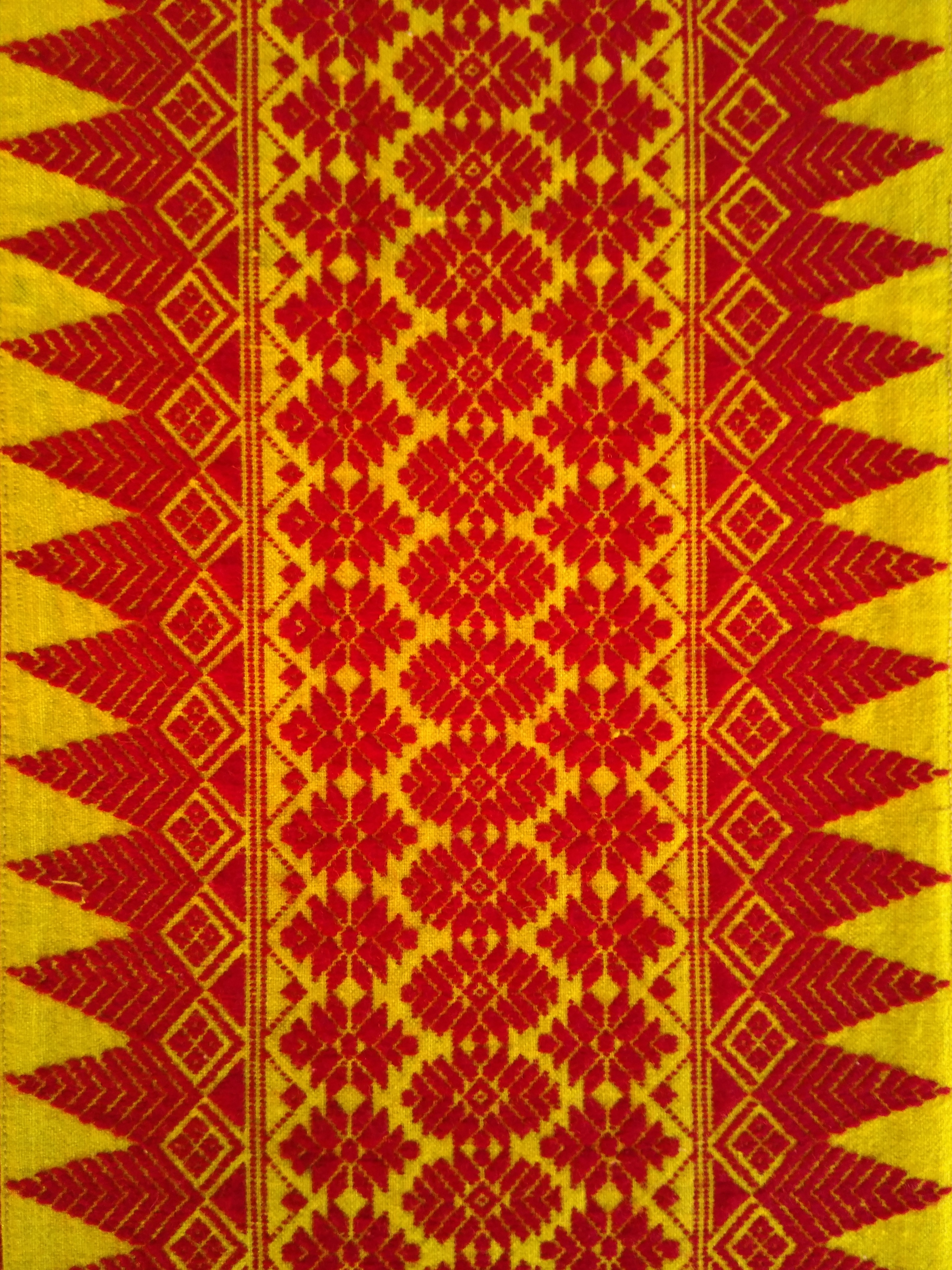 A variation of the hajw motif. Inspiration for the motifs are drawn from nature resembling the mountains, flowers, butterflies, and ferns. There are certain motifs that are especially woven in an arnai for success and health.
